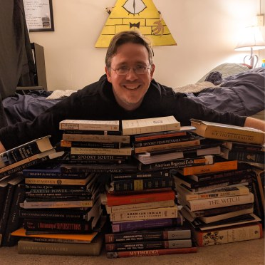Photo of author behind a short wall of books